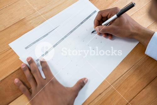 Businessman marking with pen on calendar