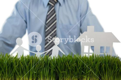 Businessman standing with paper cut out of family and house on grass