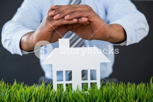 Businessman protecting paper cut out house with hand