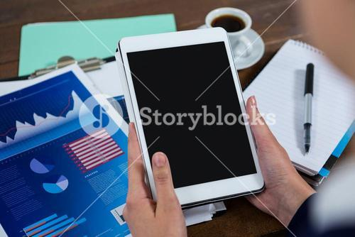 Businesswoman using digital tablet with graph chart on table