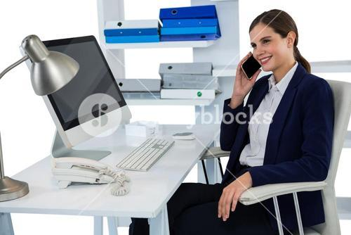 Smiling businesswoman talking on mobile phone at desk with computer