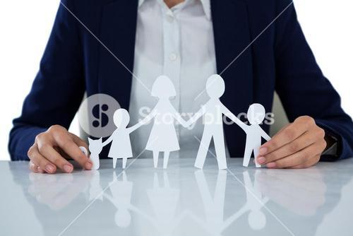 Businesswoman holding paper cut out of family