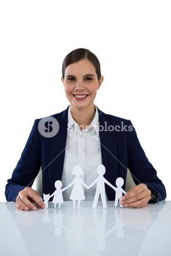 Smiling businesswoman holding paper cut out of family