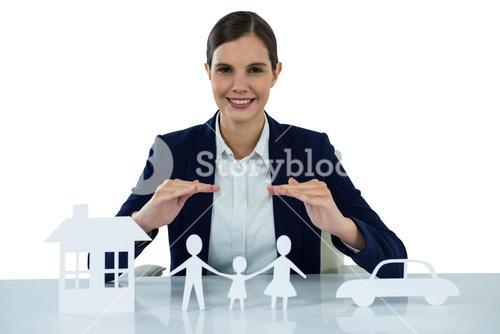Smiling businesswoman protecting paper cut out family, house and car with hands