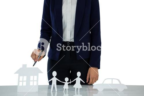 Businesswoman pointing on a paper cut out of family, car and house