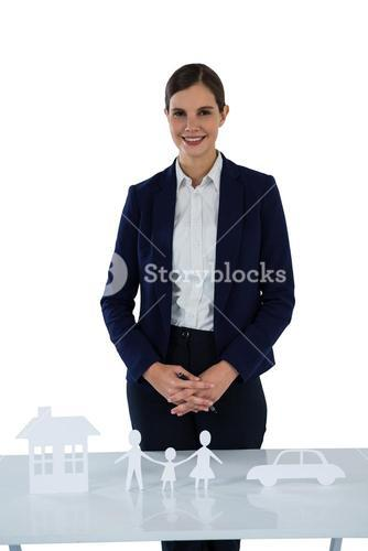 Smiling businesswoman standing with paper cut out of family, house and car on table