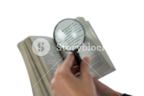 Businesswoman reading a dictionary through magnifying glass