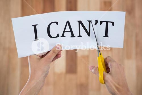 Conceptual image of businesswoman cutting a paper that reads we cant