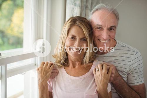 Portrait of happy senior couple standing next to window