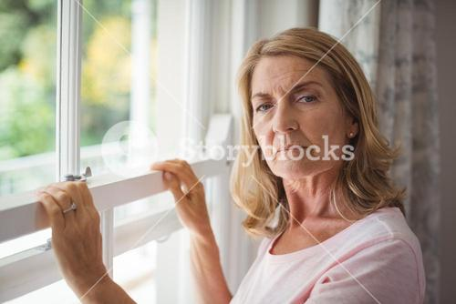 Portrait of senior woman standing next to window