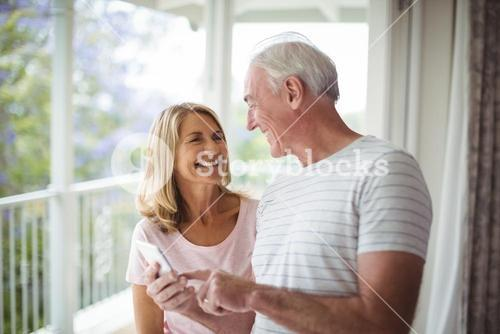 Happy senior couple interacting with each other in balcony