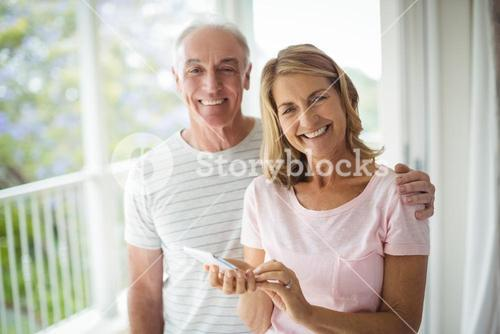 Portrait of happy senior couple standing in balcony with mobile phone