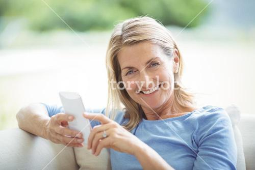 Smiling senior woman using mobile phone in living room