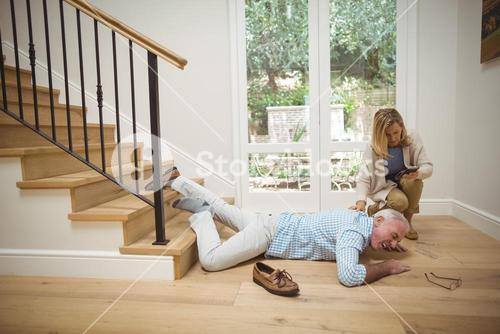 Woman checking her mobile phone while senior man fallen downstairs