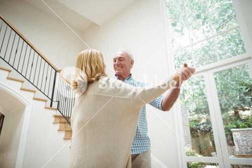 Senior couple dancing together in living room