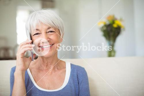 Smiling senior woman talking on mobile phone in living room