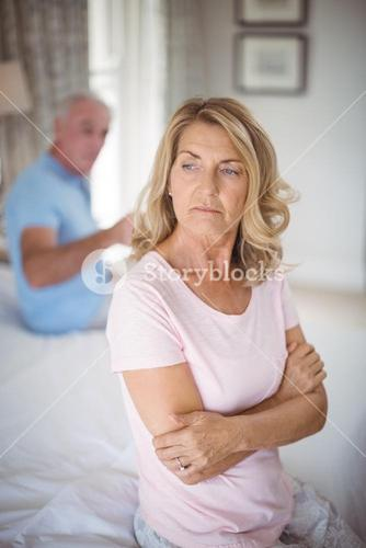 Upset senior couple arguing in bedroom