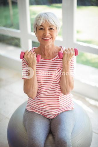 Senior woman exercising with dumbells at home