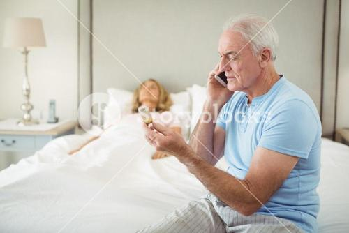 Senior man talking on mobile phone while senior woman resting in bedroom