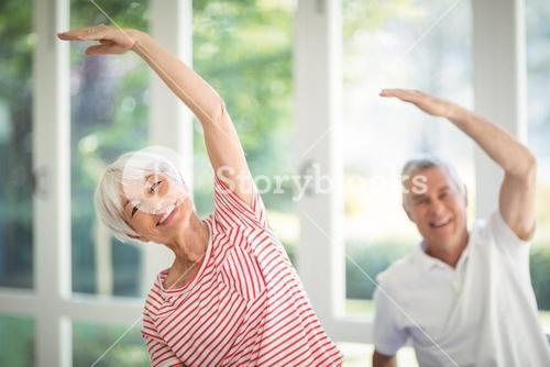 Senior couple performing stretching exercise at home