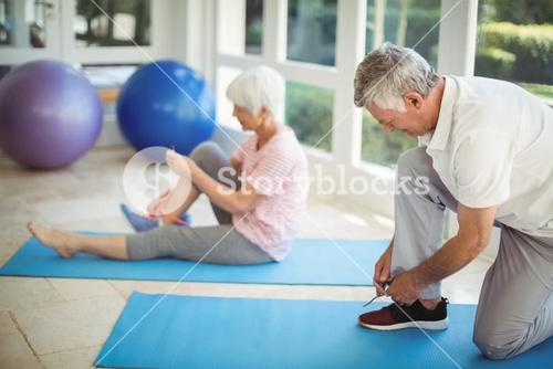 Senior couple removing their shoes at home