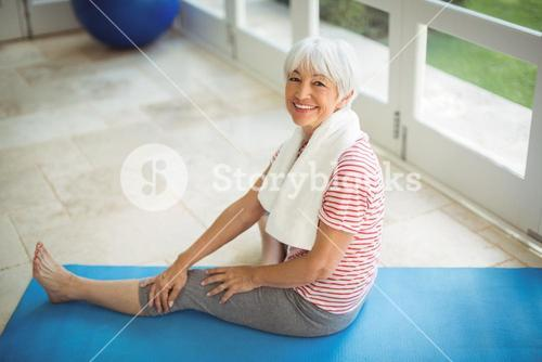 Senior woman sitting with towel at home
