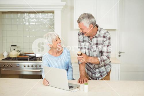 Senior couple holding medicine bottle and using laptop