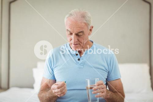 Senior man holding medicine and glass of water