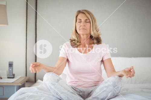 Senior practicing yoga on bed
