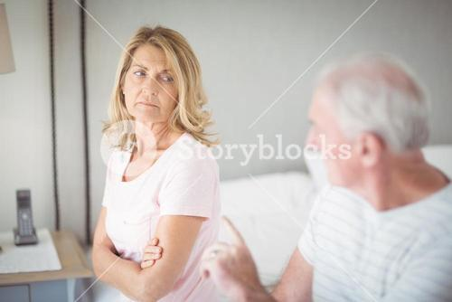 Worried senior woman sitting on bed
