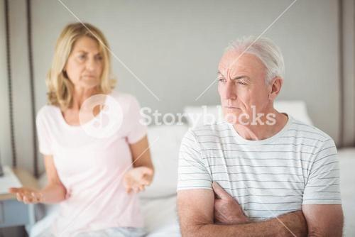 Worried senior man sitting on bed