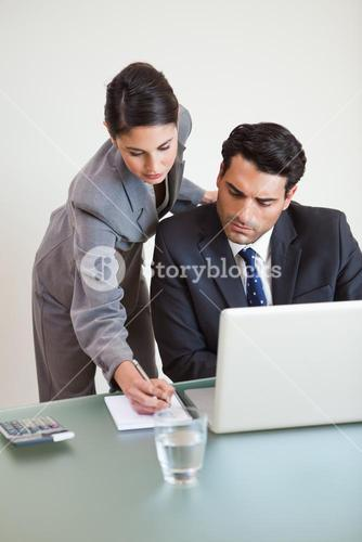 Portrait of a good looking business team working with a laptop