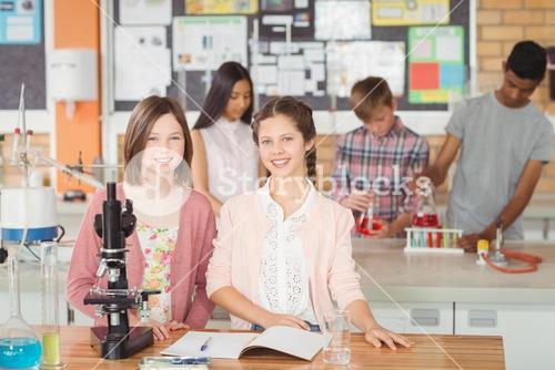 Portrait of students experimenting on microscope in laboratory
