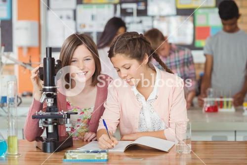 Students experimenting on microscope in laboratory