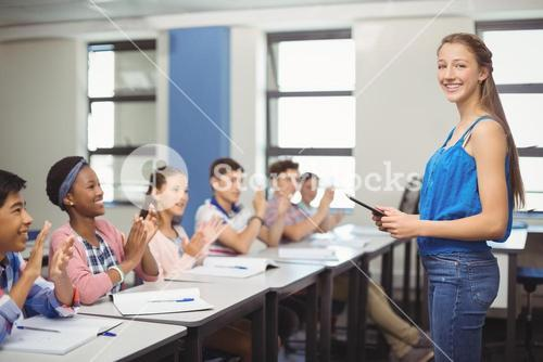 Students appreciating classmate after presentation in classroom
