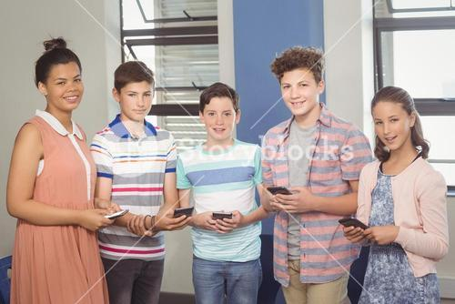 Students holding mobile phone in classroom