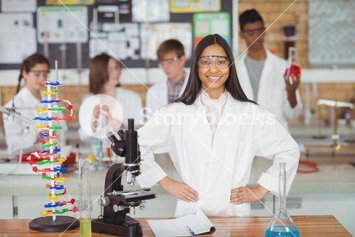 Portrait of school girl standing with hand on hip in laboratory