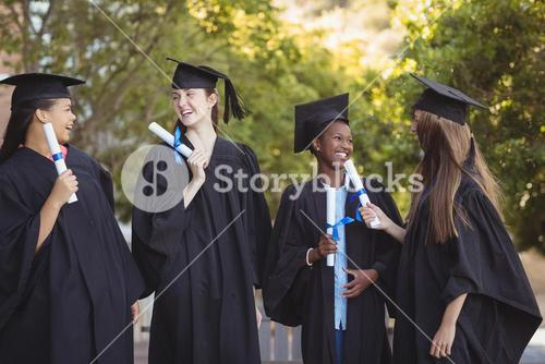 Graduate school kids standing with degree scroll in campus at school