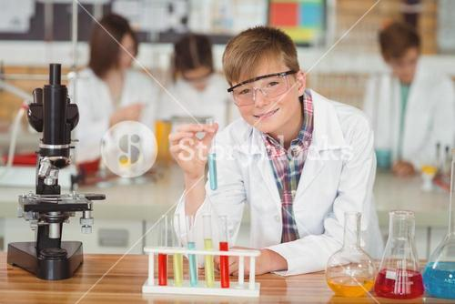 Portrait of schoolboy doing a chemical experiment in laboratory
