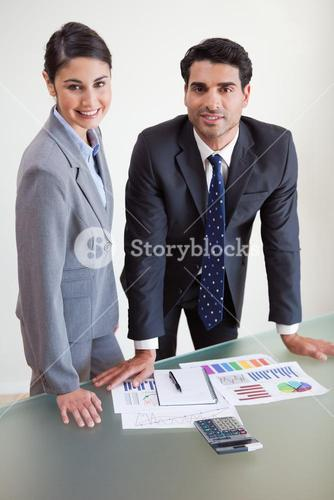 Portrait of smiling sales persons studying their results