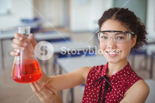 Portrait of smiling schoolgirl doing a chemical experiment in laboratory