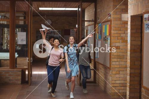 Excited classmates running with grade cards in corridor