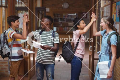 Happy classmates giving high five to each other in corridor