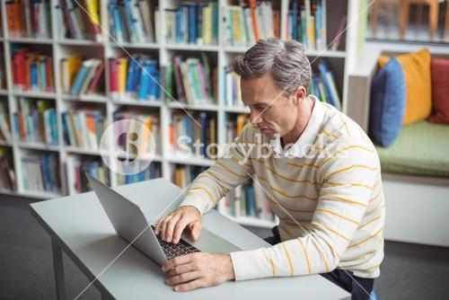 Attentive school teacher using laptop in library