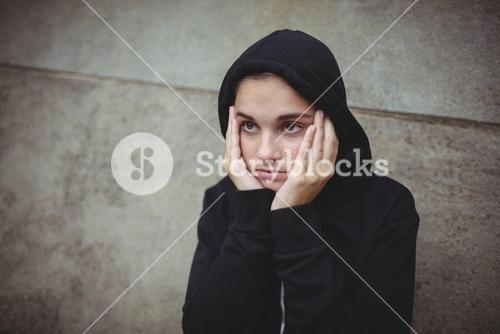 Anxious teenage girl in black hooded jacket standing with hand on face