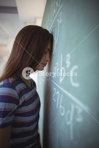 Tired schoolgirl standing with closed eyes near chalkboard in classroom
