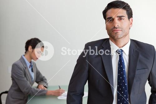 Handsome businessman posing while his colleague is working