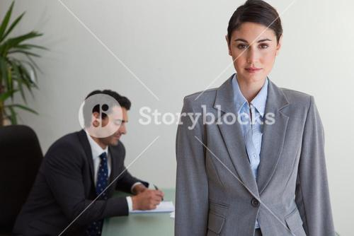 Gorgeous businesswoman posing while her colleague is working