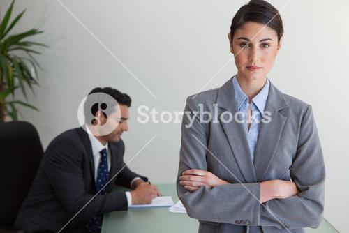 Professional businesswoman posing while her colleague is working