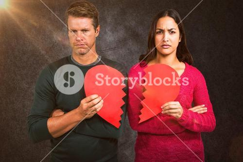Composite image of portrait of serious couple holding cracked heart shape